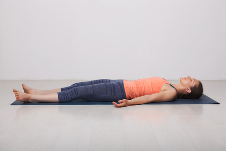 Beautiful sporty fit yogini woman relaxes in yoga asana Savasana - corpse pose in studio Imagens