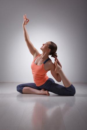 Beautiful sporty fit yogini woman practices yoga asana Eka pada rajakapotasana - one-legged pigeon pose in studio