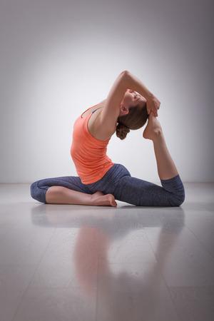 Beautiful sporty fit yogini woman practices yoga asana Eka pada rajakapotasana - one-legged king pigeon pose in studio Imagens