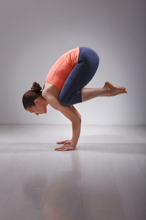 yogini: Beautiful sporty fit yogini woman practices yoga asana Bakasana - crane pose arm balance in studio