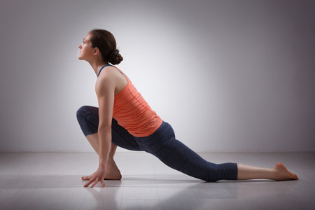 yogini: Beautiful sporty fit yogini woman practices yoga asana  Anjaneyasana - low crescent lunge pose in surya namaskar in studio Stock Photo