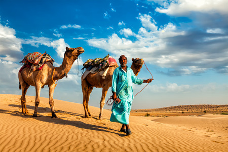 Rajasthan travel background - Indian cameleer (camel driver) with camels in dunes of Thar desert. Jaisalmer, Rajasthan, India Stock Photo