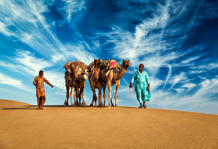 camel in desert: Rajasthan travel background - two Indian cameleers (camel drivers) with camels in dunes of Thar desert. Jaisalmer, Rajasthan, India