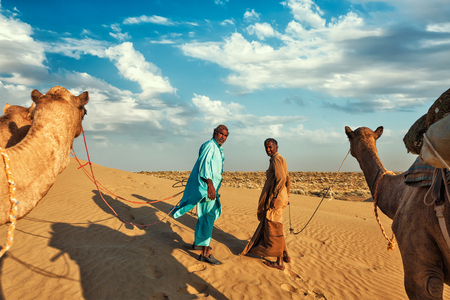 thar: Rajasthan travel background - two indian cameleers (camel drivers) with camels in dunes of Thar desert. Jaisalmer, Rajasthan, India