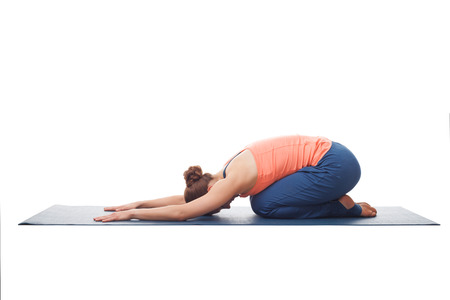 yogini: Beautiful sporty fit yogini woman practices yoga asana balasana (childs pose) - resting pose or counter asana for many asanas isolated on white