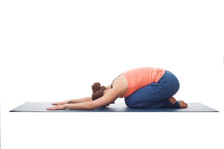 Beautiful sporty fit yogini woman practices yoga asana balasana (childs pose) - resting pose or counter asana for many asanas isolated on white