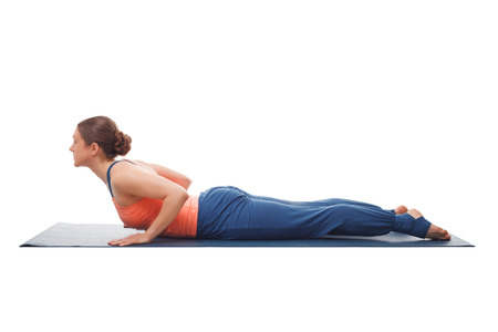 yogini: Beautiful sporty fit yogini woman practices yoga asana bhujangasana - cobra pose beginner variation isolated on white background