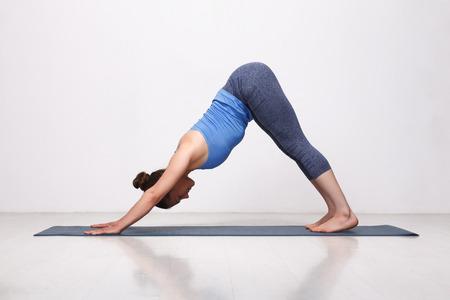 Beautiful sporty fit yogini woman practices yoga asana adhomukha svanasana - downward facing dog pose in studio