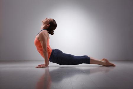 dog pose: Beautiful sporty fit yogini woman practices yoga asana urdhva mukha svanasana - upward facing dog pose in studio