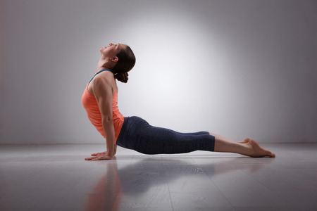 Schöne sportliche Passform yogini Frau übt Yoga Asana urdhva mukha svanasana - aufwärts Einfassungs-Hundehaltung im Studio Standard-Bild - 42870164