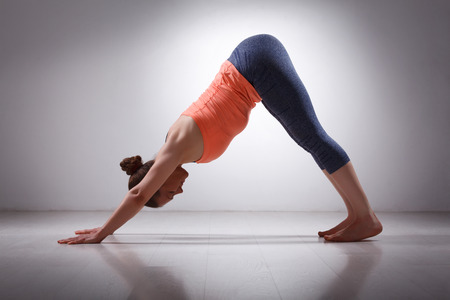 downward: Beautiful sporty fit yogini woman practices yoga asana adhomukha svanasana - downward facing dog pose in studio