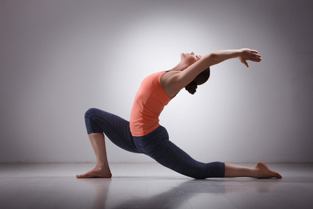 Beautiful sporty fit yogini woman practices yoga asana  Anjaneyasana - low crescent lunge pose in surya namaskar in studio Banque d'images