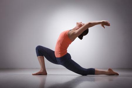 Mooie sportieve fit yogini vrouw praktijken yoga asana Anjaneyasana - laag halve lunge poseren Surya Namaskar in studio