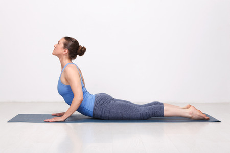 Beautiful sporty fit yogini woman practices yoga asana bhujangasana - cobra pose in studio Фото со стока