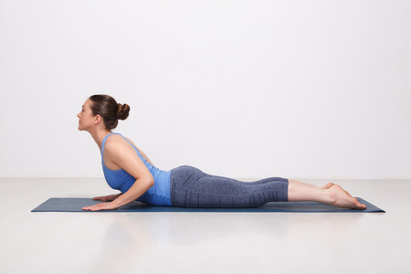 yogini: Beautiful sporty fit yogini woman practices yoga asana bhujangasana - cobra pose beginner variation in studio Stock Photo