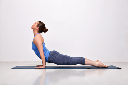 Beautiful sporty fit yogini woman practices yoga asana urdhva mukha svanasana - upward facing dog pose in studio
