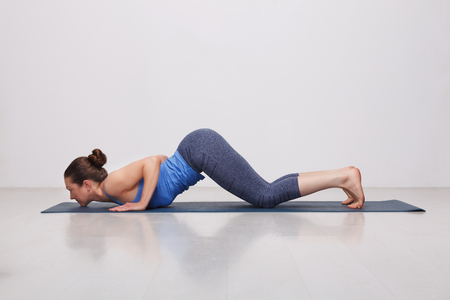yogini: Beautiful sporty fit yogini woman practices yoga asana Ashtangasana - eight-limbed pose variation in studio Stock Photo
