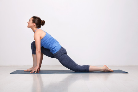 Beautiful sporty fit yogini woman practices yoga asana  Anjaneyasana - low crescent lunge pose in surya namaskar in studio Stock Photo