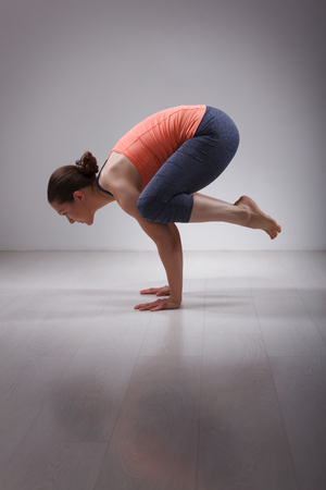 yogini: Beautiful sporty fit yogini woman practices yoga asana kakasana - crow pose in studio