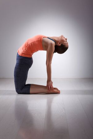 Beautiful sporty fit yogini woman practices yoga asana ustrasana - camel pose in studio Stock Photo