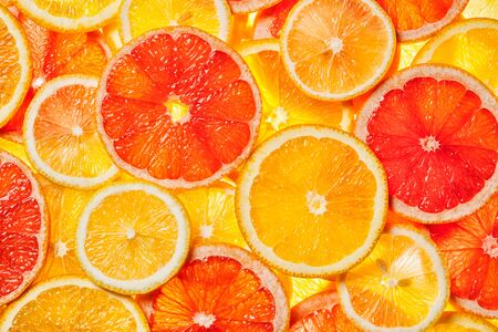 Colorful citrus fruit - lemon, orange, grapefruit - slices background. Backlit Фото со стока