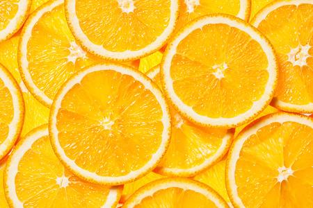 カラフルなオレンジの柑橘系フルーツのスライスはバックライトを背景します。