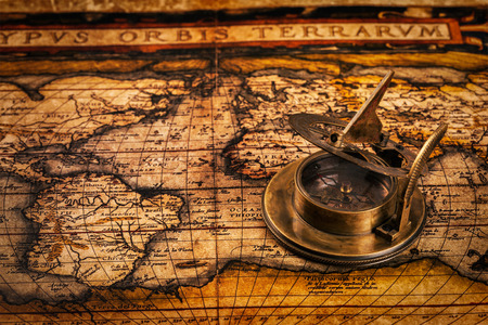 Travel geography navigation concept background - old vintage retro compass with sundial on ancient world map