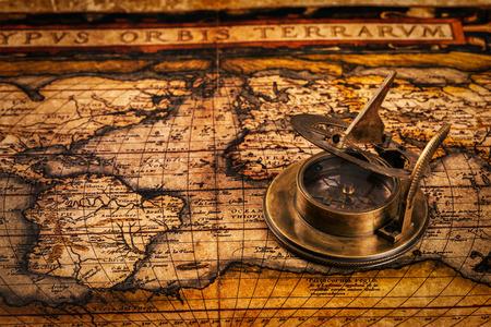 cadran solaire: Voyage g�ographie concept de la navigation fond - vieux compas r�tro vintage avec cadran sur l'ancienne carte du monde