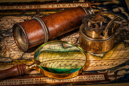 sundial: Travel geography navigation concept background - old vintage retro compass with sundial, spyglass and magnifying glass on ancient world map