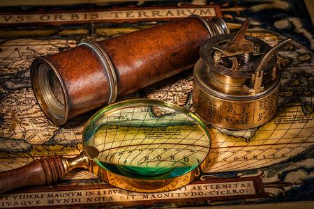 reloj de sol: Viaja geografía concepto de navegación de fondo - viejo compás retro vendimia con el reloj de sol, el catalejo y una lupa sobre el antiguo mapa del mundo