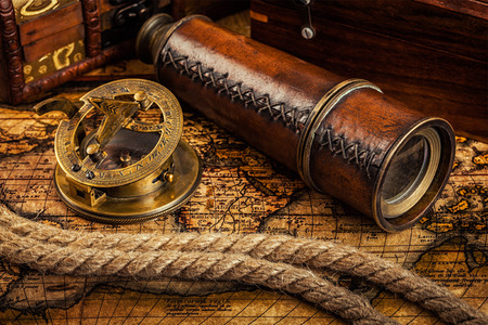 sundial: Travel geography navigation concept background - old vintage retro compass with sundial, spyglass and rope on ancient world map