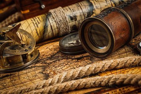brujula: Viajes geograf�a concepto de navegaci�n de fondo - viejo comp�s retro vendimia con el reloj de sol, el catalejo y cuerda en la antigua mapa del mundo