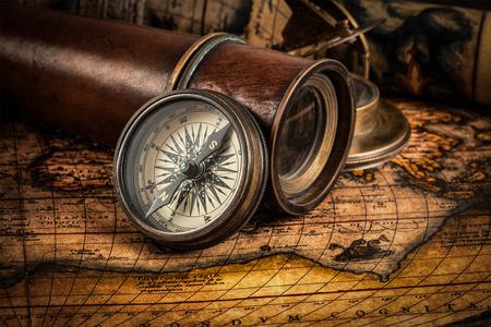 Reizen aardrijkskunde navigatie concept achtergrond - oude vintage retro kompas met zonnewijzer, verrekijker en touw op de oude kaart van de wereld Stockfoto