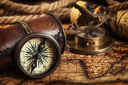 sun dial: Travel geography navigation concept background - old vintage retro compass with sundial, spyglass and rope on ancient world map