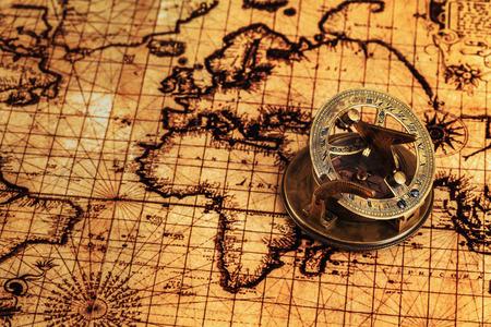 sonnenuhr: Reisen Geographie Navigationskonzept Hintergrund - alte Vintage retro-Kompass mit Sonnenuhr auf antiken Weltkarte Lizenzfreie Bilder