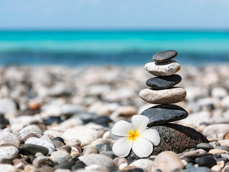 Zen meditation spa relaxation background -  balanced stones stack with frangipani plumeria flower close up on sea beach