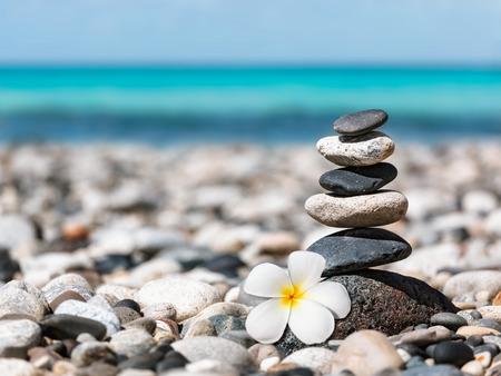 Zen meditation spa relaxation background -  balanced stones stack with frangipani plumeria flower close up on sea beach