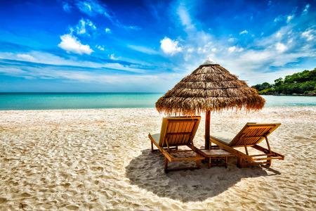 strandstoel: Vakantie vakantie achtergrond behang - twee strand ligstoelen onder tent op strand. Sihanoukville, Cambodja Stockfoto