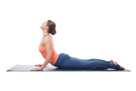 Beautiful sporty fit yogini woman practices yoga asana bhujangasana - cobra pose isolated on white background