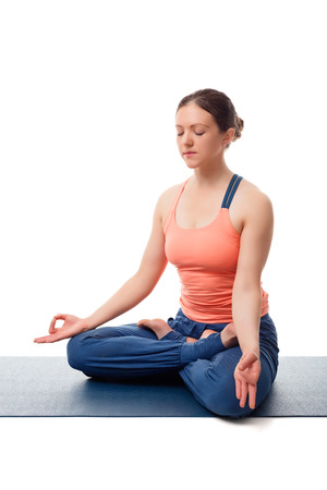 yogic: Beautiful fit yogini woman meditating in yoga asana Padmasana (Lotus pose) cross legged position for meditation with Chin Mudra - psychic gesture of consciousness, isolated on white background Stock Photo