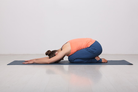 Beautiful sporty fit yogini woman practices yoga asana balasana (child's pose) - resting pose or counter asana for many asanas in studio Banco de Imagens