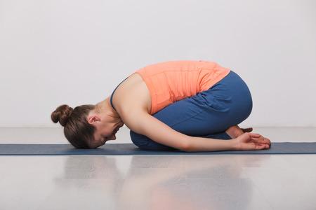 Beautiful sporty fit yogini woman practices yoga asana balasana (child's pose) - resting pose or counter asana for many asanas in studio Standard-Bild