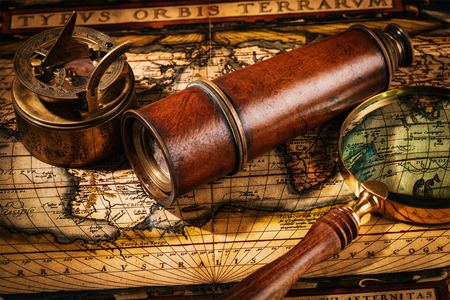 magnify: Travel geography navigation concept background - old vintage retro compass with sundial, spyglass and magnifying glass on ancient world map
