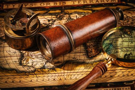 lupa: Viaja geografía concepto de navegación de fondo - viejo compás retro vendimia con el reloj de sol, el catalejo y una lupa sobre el antiguo mapa del mundo