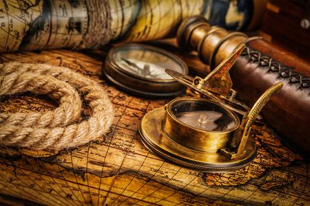 navegacion: Viajes geografía concepto de navegación de fondo - viejo compás retro vendimia con el reloj de sol, el catalejo y cuerda en la antigua mapa del mundo