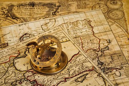 reloj de sol: Viaja geografía concepto de navegación de fondo - viejo compás retro vendimia con el reloj de sol en la antigua mapa del mundo Foto de archivo