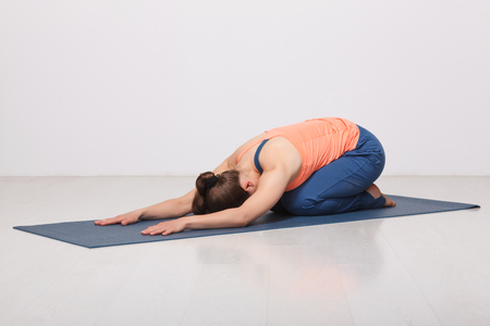 childs: Beautiful sporty fit yogini woman practices yoga asana balasana (childs pose) - resting pose or counter asana for many asanas in studio
