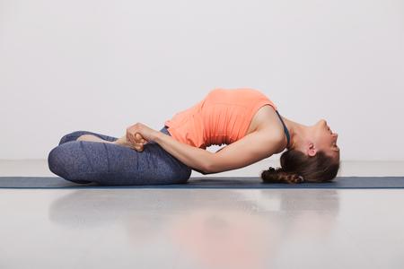 Schöne sportliche Passform yogini Frau übt Yoga Asana Matsyasana - Fische werfen im Studio