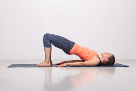 beginner: Beautiful sporty fit yogini woman practices yoga asana setu bandhasana - bridge pose beginner variation in studio