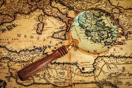 Travel geography navigation concept background - old vintage retro magnifying glass on ancient Mediterranean sea  map